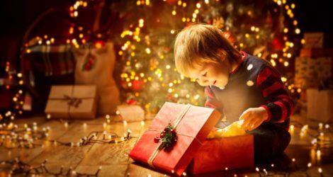 Kind öffnet Geschenke an Weihnachten
