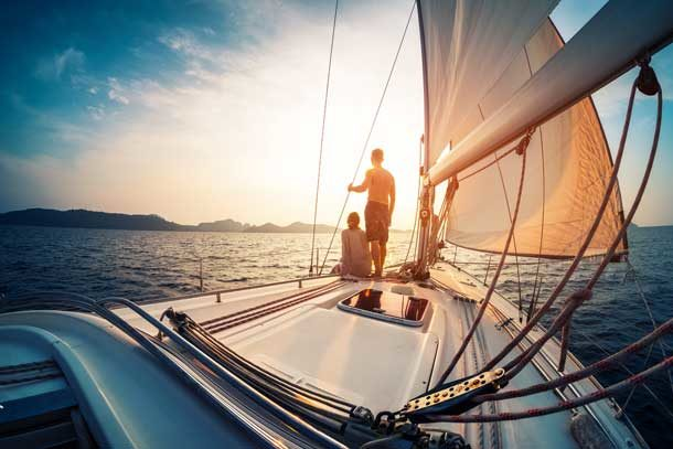 Pärchen schaut in den Sonnenuntergang auf einer Yacht.