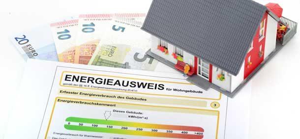 Zu sehen sind ein Energieausweisformular, Geldscheine und ein Modellhaus