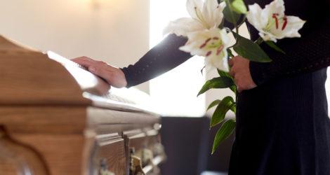 In schwarz gekleidete Frau trauert am Sarg mit Lilien in der Hand.
