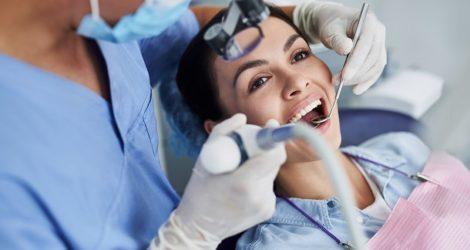 Frau sitzt beim Zahnarzt und bekommt eine Prophylaxe
